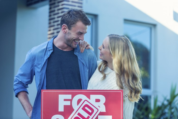 Couple standing in front of a new home
